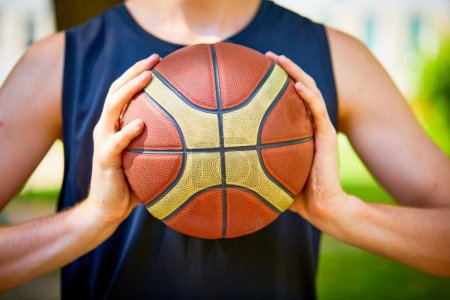 man holding basketball ball, close-up