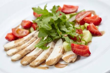 chicken fillet with salad on white plate, close-up