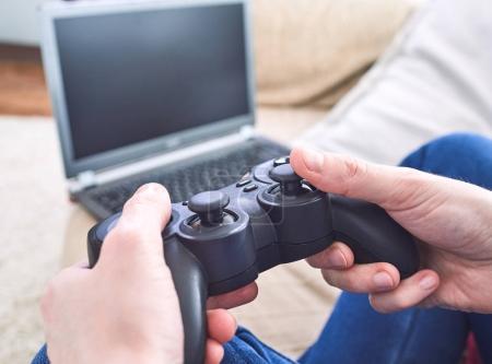homme tenant des contrôleurs de la manette tout en jouant à des jeux vidéo à la maison