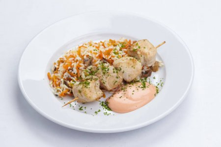 chicken kebab with rice on white plate, close-up
