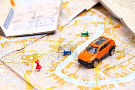 small toy car with pins on map, travel concept