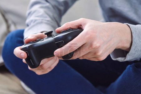 Photo for Man holding joystick controllers while playing video games at home - Royalty Free Image