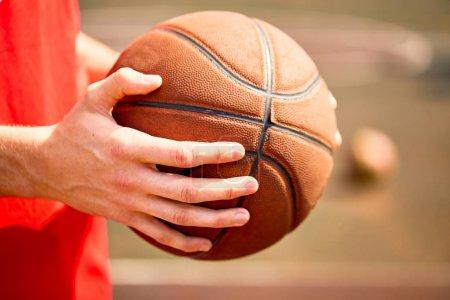 man holding basketball ball, close-up