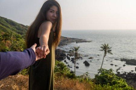 Photo pour Prise de vue d'une jeune femme conduisant quelqu'un par la main à la plage - image libre de droit
