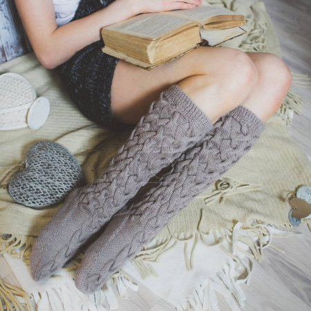 Foto de Noche de invierno acogedor, calcetines de lana caliente. Mujer relajante en casa, leyendo un libro. Cómodo estilo de vida. - Imagen libre de derechos