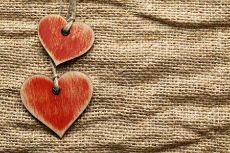 Wooden hearts on fabric background