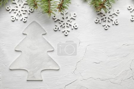 White Christmas tree, snowflakes and spruce tree on plastered wa