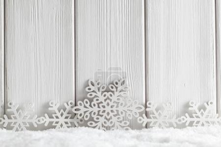 Christmas background - white snowflakes on snow and wooden plank