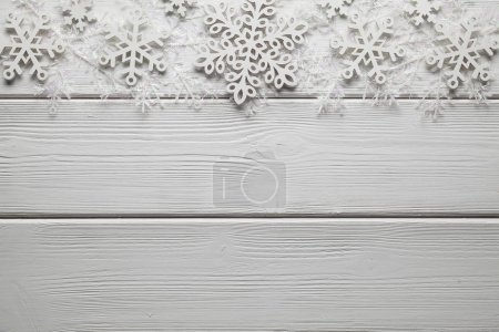 Christmas decorations - white snowflakes on wooden background