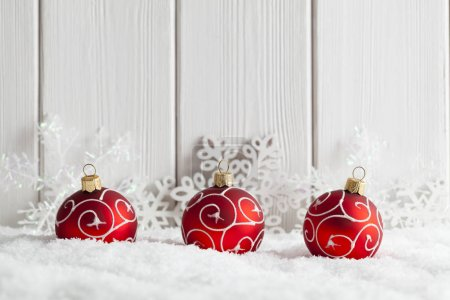 Christmas background - baubles and snowflakes on snow and white