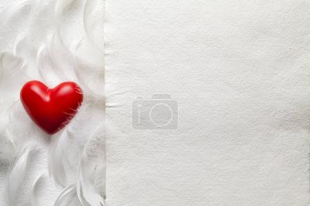 One red heart, feathers and white handmade paper sheet