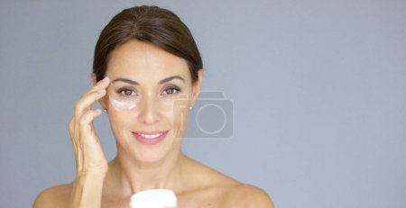 Beautiful young woman applying face cream