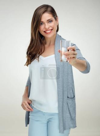 smiling woman with long hair holding water glass against light background