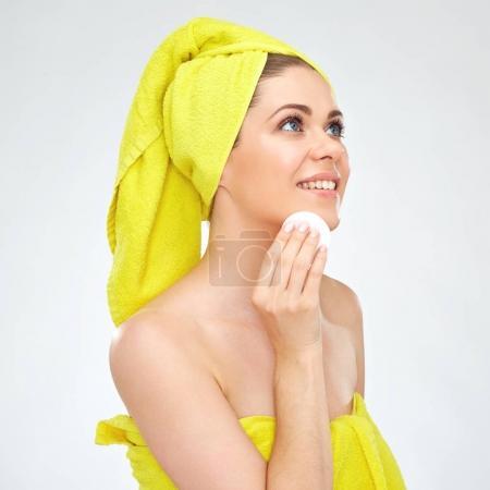 sonriente a mujer atractiva en toallas azul con cojín de algodón para limpieza de cutis