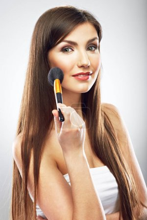 smiling beautiful woman applying make up with brush