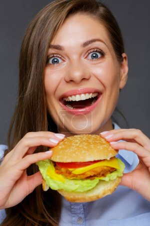happy woman with open mouth holding big burger