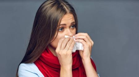 Sickness woman blow on nose in paper tissue.