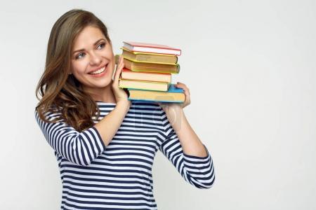 Smiling student girl holding pile of books.