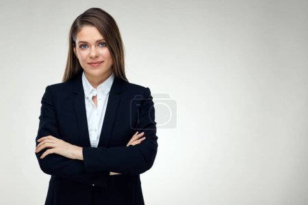 classic business portrait of young woman with crossed arms on dark grey wall background