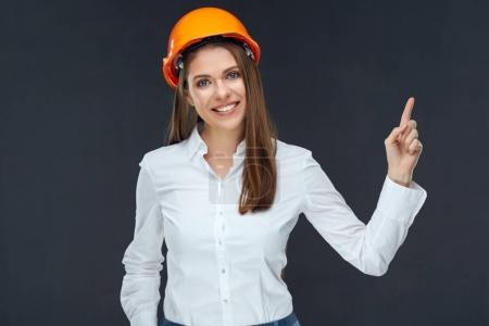 woman builder in helmet pointing finger at copy space on black background