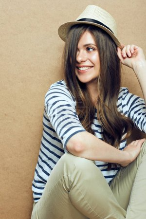 woman wearing striped shirt and hipster hat sitting near beige wall background