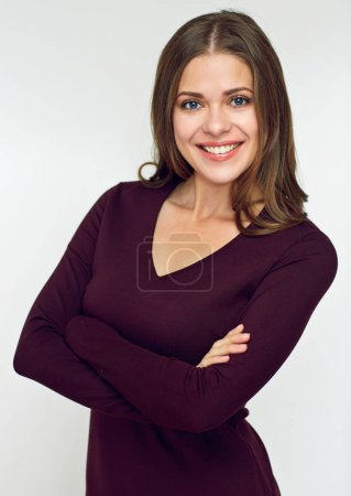 smiling woman wearing brown dress standing with crossed arms