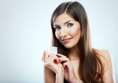 Smiling girl holding beauty skin care cream in glass jar.