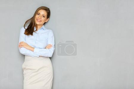 confident businesswoman standing against wall with crossed arms