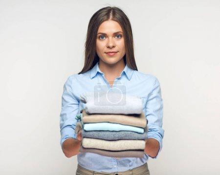 Smiling woman holding stack of warm winter clothes.