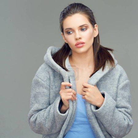 beautiful female fashion model wearing gray coat with deep hood posing on gray background