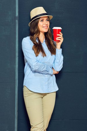 young woman in hat drinking coffee from red cup and standing near black wall