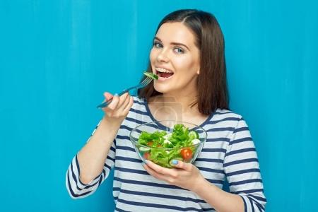 smiling young woman eating diet food green salad, healthy food concept