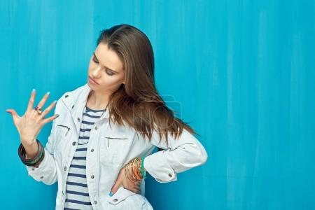 Teen girl looking at jewelry rings on fingers.