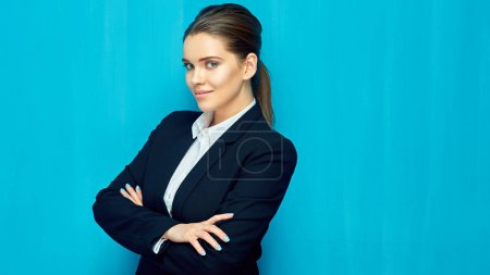 smiling businesswoman wearing black suit standing with crossed arms on blue wall background