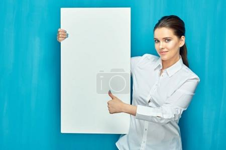 smiling woman holding big white sign board and showing thumb up on blue wall background