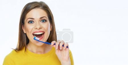 portrait of toothy smiling woman holding toothy brush, teeth health concept