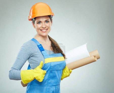 Photo pour Architecte constructeur femme dans protéger casque tenant des plans et montrant pouce vers le haut sur fond gris - image libre de droit