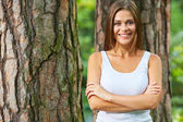 Smiling woman with crossed arms standing in forest