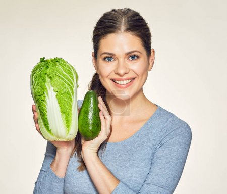 portrait  of beautiful young woman holding cabbage and avocado