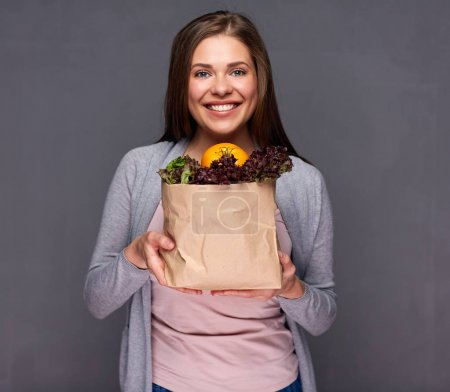 Smiling woman holding paper bag with summer vegeta...
