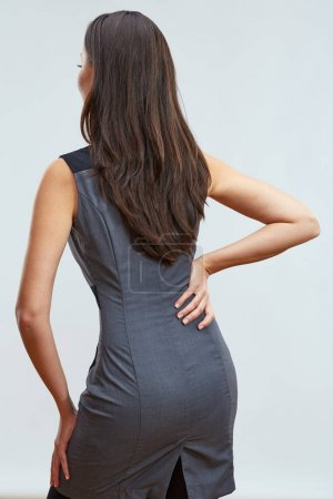 businesswoman  in corporate style dress touching back with pain, concept of occupational diseases office worker