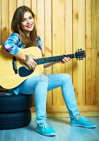 Photo for Smiling hipster woman sitting car tires with guitar on wooden wall background - Royalty Free Image