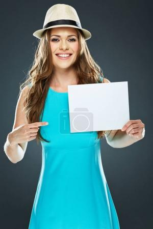 young smiling woman pointing finger at white banner