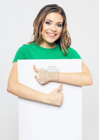 portrait of smiling woman holding white blank sign board and showing thumb up