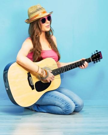 fashion music look with young model in sunglasses and hat sitting on blue floor and playing acoustic guitar