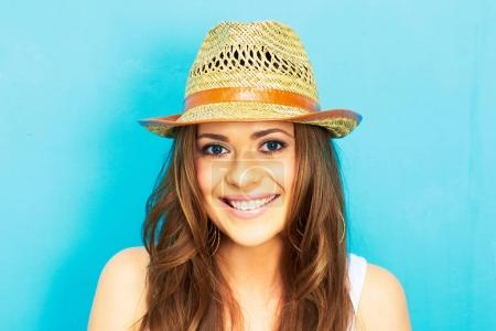 Photo for Beautiful happy woman with straw hat smiling and looking at camera on blue background - Royalty Free Image