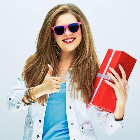 happy smiling woman holding red gift and showing thumb up on white studio background