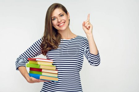 smiling student woman holding pile of books and pointing with finger on copy space