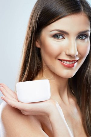 smiling attractive woman holding jar cream