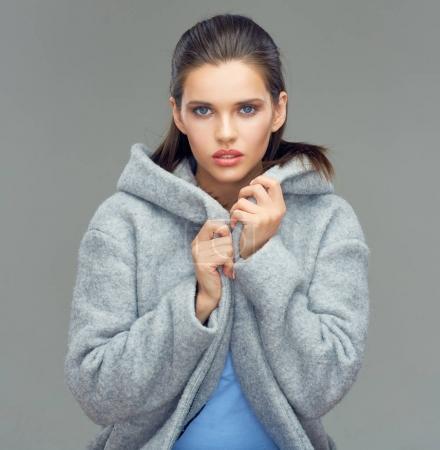 Photo pour Portrait de jeune femme de beauté portant un manteau gris avec une grande capuche - image libre de droit